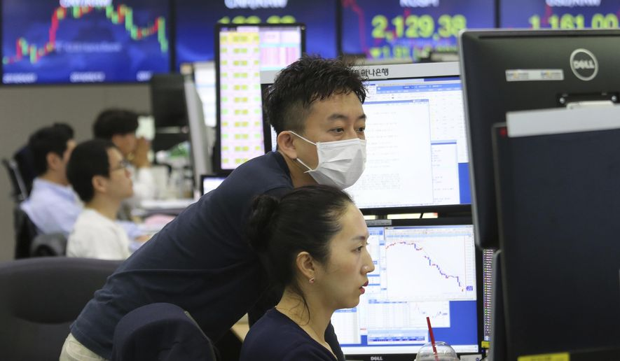 Currency traders watch monitors at the foreign exchange dealing room of the KEB Hana Bank headquarters in Seoul, South Korea, Friday, June 21, 2019. Shares retreated in Asia on Friday after a broad rally for stocks drove the S&P 500 index to an all-time high as weak manufacturing data from Japan helped dampen investor sentiment. (AP Photo/Ahn Young-joon)