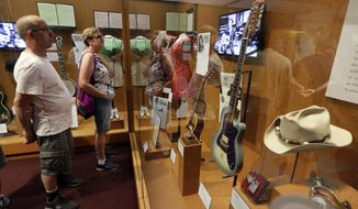 FILE - In this May 25, 2018 photo, visitors to the Country Music Hall of Fame and Museum in Nashville, Tenn. view the the Outlaws & Armadillos exhibit. Tourism comes alive in the Music City come summer, and many of the city's Nashville-based stars enjoying playing tourist, too. (AP Photo/Mark Humphrey, File)