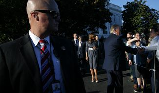 President Donald Trump, right, with first lady Melania Trump, center, greet attendees of the annual Congressional Picnic on the South Lawn of the White House, Friday, June 21, 2019, in Washington, as a Secret Service Agent watches at left. (AP Photo/Jacquelyn Martin)