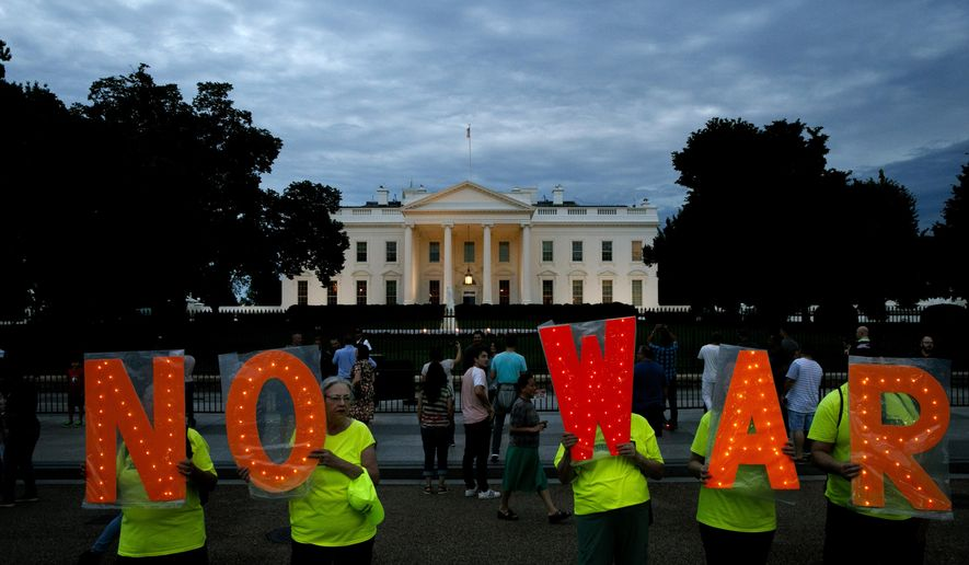 Protesters hold signs spelling out, 'No War' outside the White House, Thursday June 20, 2019, in Washington, after President Donald Trump tweeted that 'Iran made a very big mistake' by shooting down a U.S. surveillance drone over the Strait of Hormuz in Iran. (AP Photo/Jacquelyn Martin)