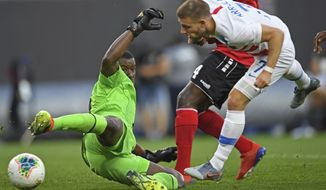 Trinidad and Tobago goalkeeper Marvin Phillip deflects the ball after a shot by U.S. forward Paul Arriola during the first half of a CONCACAF Gold Cup soccer match Saturday, June 22, 2019, in Cleveland. (AP Photo/David Dermer)