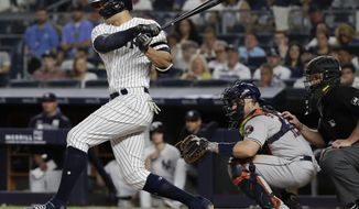 New York Yankees' Giancarlo Stanton follows through on a two-run single during the seventh inning of a baseball game as Houston Astros' catcher Max Stassi watches, Saturday, June 22, 2019, in New York. (AP Photo/Frank Franklin II)