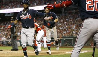 Atlanta Braves' Ronald Acuna Jr., left, and Dansby Swanson celebrate with teammate Josh Donaldson after scoring on Freddie Freeman's single in the fifth inning of a baseball game against the Washington Nationals, Saturday, June 22, 2019, in Washington. (AP Photo/Patrick Semansky)