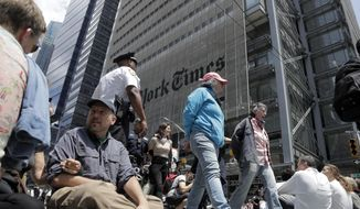 Activists sit on an intersection as others are taken into custody by New York Police officers during a climate change rally outside of the New York Times building, Saturday, June 22, 2019, in New York. Activists blocked traffic along 8th Avenue during a sit-in to demand coverage of climate change by the newspaper. (AP Photo/Julio Cortez)