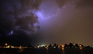 FILE - In this Aug. 10, 2016, file photo, lightning streaks across the night sky as a monsoon storm sweeps through the Phoenix metro area. Arizona's monsoon season is quickly approaching.  ADOT plans to begin installing the new dust-detection system early this fall 2019.  The system includes long-range radar set near Picacho Peak that can detect approaching dust storms from 50 miles out and short-range radars to detect dust particles, set every mile between areas where most of the I-10 crashes occur. (AP Photo/Ross D. Franklin, File)