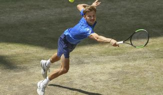 Belgium's David Goffin is hitting a ball against Italy's Berrettini during the semifinal at the ATP tennis tournament in Halle, Germany, June 22, 2019. (Friso Gentsch/dpa via AP)