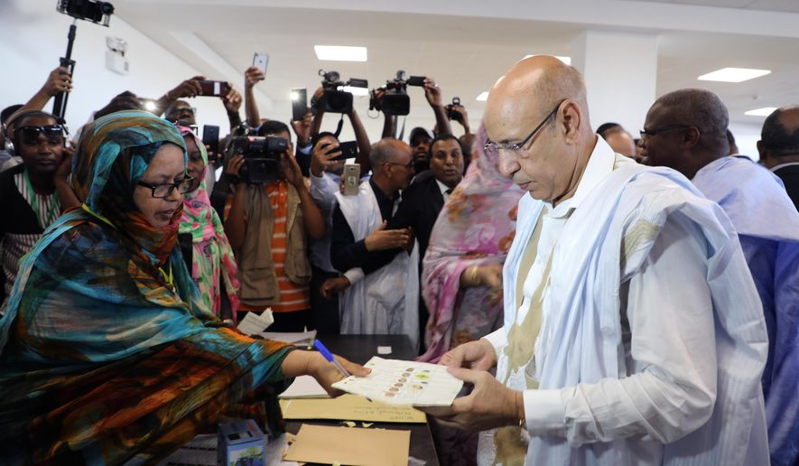 Ruling party presidential candidate and former Defense Minister Mohamed Ould El Ghazouani casts his ballot in Nouakchott, Mauritania, Saturday June 22, 2019. Mauritanians are choosing between outgoing President Mohamed Ould Abdel Aziz's heir apparent and five opposition candidates who believe the front-runner would represent a continuation of his rule in this West African country battling Islamic extremism. (AP Photo/Elhady Ould Mohamedou)