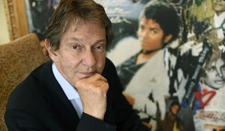 "In this Tuesday, June 18, 2019 photo, Entertainment and corporate lawyer John Branca, the co-executor of Michael Jackson's estate, poses in his office next to an artwork presented to him from Sony Music commemorating the sale of 100 million copies of Michael Jackson's album ""Thriller,""  at the law firm of Ziffren Brittenham LLP in Los Angeles. (AP Photo/Chris Pizzello)"