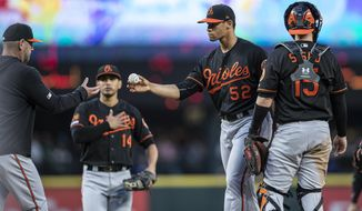 Baltimore Orioles relief pitcher Branden Kline, second from right, is pulled from a baseball game against the Seattle Mariners in the fifth inning by manager Brandon Hyde, left, as third baseman Rio Ruiz and catcher Chance Sisco stand at the mound Friday, June 21, 2019, in Seattle. (AP Photo/Stephen Brashear)