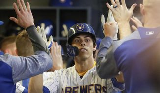 Milwaukee Brewers' Christian Yelich is congratulated after hitting a two-run home run during the fifth inning of a baseball game against the Cincinnati Reds Friday, June 21, 2019, in Milwaukee. (AP Photo/Morry Gash)