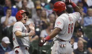 Cincinnati Reds' Derek Dietrich congratulates Yasiel Puig after his two-run home run during the eighth inning of a baseball game against the Milwaukee Brewers Friday, June 21, 2019, in Milwaukee. (AP Photo/Morry Gash)
