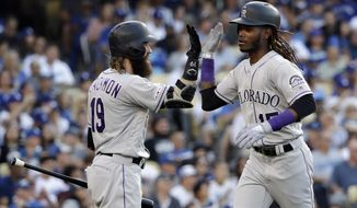 Colorado Rockies' Raimel Tapia, right, celebrates his solo home run with Charlie Blackmon during the seventh inning of the team's baseball game against the Los Angeles Dodgers on Saturday, June 22, 2019, in Los Angeles. (AP Photo/Marcio Jose Sanchez)