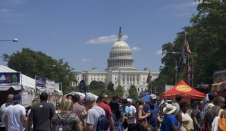 Hundreds of people gather on Pennsylvania Avenue on Saturday for the 27th annual Giant National Capital Barbecue Battle. The event raised more than $1 million for the USO of Metropolitan Washington-Baltimore. (Moss Brennan/The Washington Times)