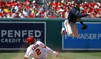 Atlanta Braves shortstop Dansby Swanson, right, throws to first base for a double play after forcing out Washington Nationals' Adam Eaton at second on Anthony Rendon's ground ball to end the eighth inning of a baseball game, Sunday, June 23, 2019, in Washington. Atlanta won 4-3. (AP Photo/Patrick Semansky)
