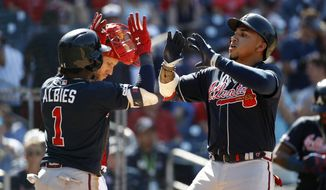 Atlanta Braves' Johan Camargo, right, and Ozzie Albies celebrate after Camargo batted Albies in on a two-run home run in the 10th inning of a baseball game against the Washington Nationals, Sunday, June 23, 2019, in Washington. (AP Photo/Patrick Semansky)