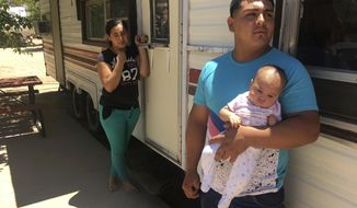 In this May 25, 2018 photo, Jose Espinoza, 18, stands out his trailer with his 4-month-old infant, Emmily, and wife, Maria Rodriguez, 19, in Vado, N.M. while speaking about making only $50 a day picking onions. The U.S. Census Bureau is using new high tech tools like aerial imagery to help get an accurate 2020 Census and avoid undercounting communities struggling with poverty. (AP Photo/Russell Contreras)