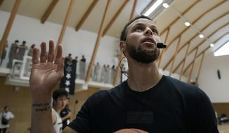 Golden State Warriors' Stephen Curry waves toward the fans while coaching at a high school basketball camp Sunday, June 23, 2019, in Tokyo. Curry is already looking ahead to the next challenge in his basketball career, including the chance to represent the United States at next year's Tokyo Olympics. (AP Photo/Jae C. Hong)