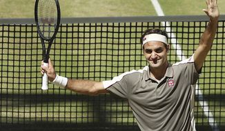 Swiss Roger Federer celebrates after winning the tennis ATP final against Belgium David Goffin in Halle, Germany, Sunday, June 23, 2019.  (Friso Gentsch/dpa via AP)