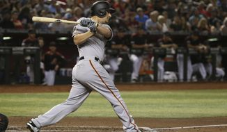 San Francisco Giants' Alex Dickerson follow through on a two-run double against the Arizona Diamondbacks during the third inning of a baseball game Saturday, June 22, 2019, in Phoenix. (AP Photo/Ross D. Franklin)