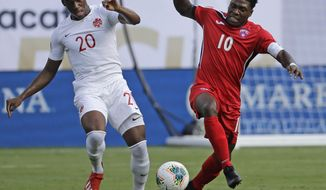 Canada's Jonathan David (20) battles Cuba's Aricheell Hernandez (10) during the first half of their CONCACAF Golf Cup soccer match in Charlotte, N.C., Sunday, June 23, 2019. (AP Photo/Chuck Burton)