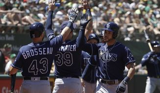 Tampa Bay Rays' Tommy Pham, right, is congratulated by teammates after scoring against the Oakland Athletics during the fourth inning of a baseball game in Oakland, Calif., Sunday, June 23, 2019. (AP Photo/Jeff Chiu)