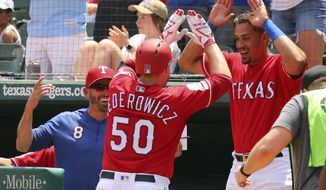 Texas Rangers manager Chris Woodward (8) and Ronald Guzman (11) celebrate the solo home run by Tim Federowicz (50) in the second inning against the Chicago White Sox in a baseball game Sunday, June 23, 2019. (AP Photo/ Richard W. Rodriguez)