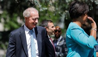 In this May 31, 2019, file photo, Washington Metropolitan Area Transit Authority Chair and D.C. Council Member Jack Evans, joins Washington, D.C., Mayor Muriel Bowser, right, at the podium during a news conference announcing a dedicated bus lane in downtown Washington. FBI agents searched Evans' Washington home on Friday, one day after he resigned from the Washington Metropolitan Area Transit Authority after a legal memo became public and verified that he violated board ethics. (AP Photo/Pablo Martinez Monsivais) ** FILE **