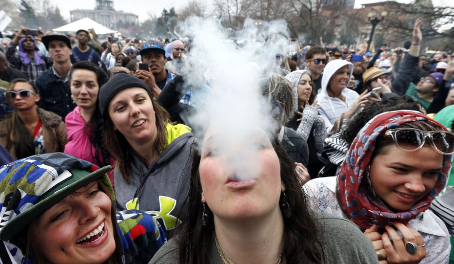 In this April 19, 2014, file photo, partygoers dance and smoke pot on the first of two days at the annual 4/20 marijuana festival in Denver. The annual event is the first 4/20 marijuana celebration since retail marijuana stores began selling in January 2014. (AP Photo/Brennan Linsley, File)