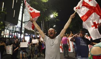 An opposition demonstrator waves Georgian national flags as he and others march on the main street near the Georgian parliament building in Tbilisi, Georgia, Monday, June 24, 2019. Thousands of protesters have convened outside the building, calling for the resignation of the interior minister and for changes in the election code. (AP Photo/Zurab Tsertsvadze)