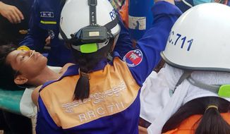 In this photo provided by the Preah Sihanouk Provincial Authority, rescuers carry a survivor from the site of a collapsed building Monday, June 24, 2019, in Preah Sihanouk province, Cambodia. Rescuers on Monday found two survivors in the rubble of a building two days after it collapsed while under construction in a Cambodian beach town, killing at least 28 workers and injuring 26 others as they slept in the unfinished condominium that was doubling as their housing. (Preah Sihanouk provincial authorities via AP)