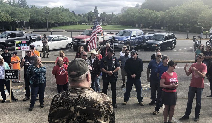 "In this photo taken Sunday, June 23, 2019, a small crowd of local Republicans show their support of a Republican walkout outside the Oregon State Capitol in Salem, Ore. The gathering took place only a day after the Senate President ordered the statehouse to close over a ""possible militia threat,"" the latest escalation in a Republican walkout over proposed climate policy that has put Democrats' top legislative priorities at risk. (AP Photo/Sarah Zimmerman)"