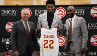 Atlanta Hawks first-round NBA basketball draft pick Cam Reddish of Duke holds his jersey as he poses with general manager Travis Schlenk, left, and head coach Lloyd Pierce during a news conference Monday, June 24, 2019, in Atlanta. (AP Photo/John Bazemore)
