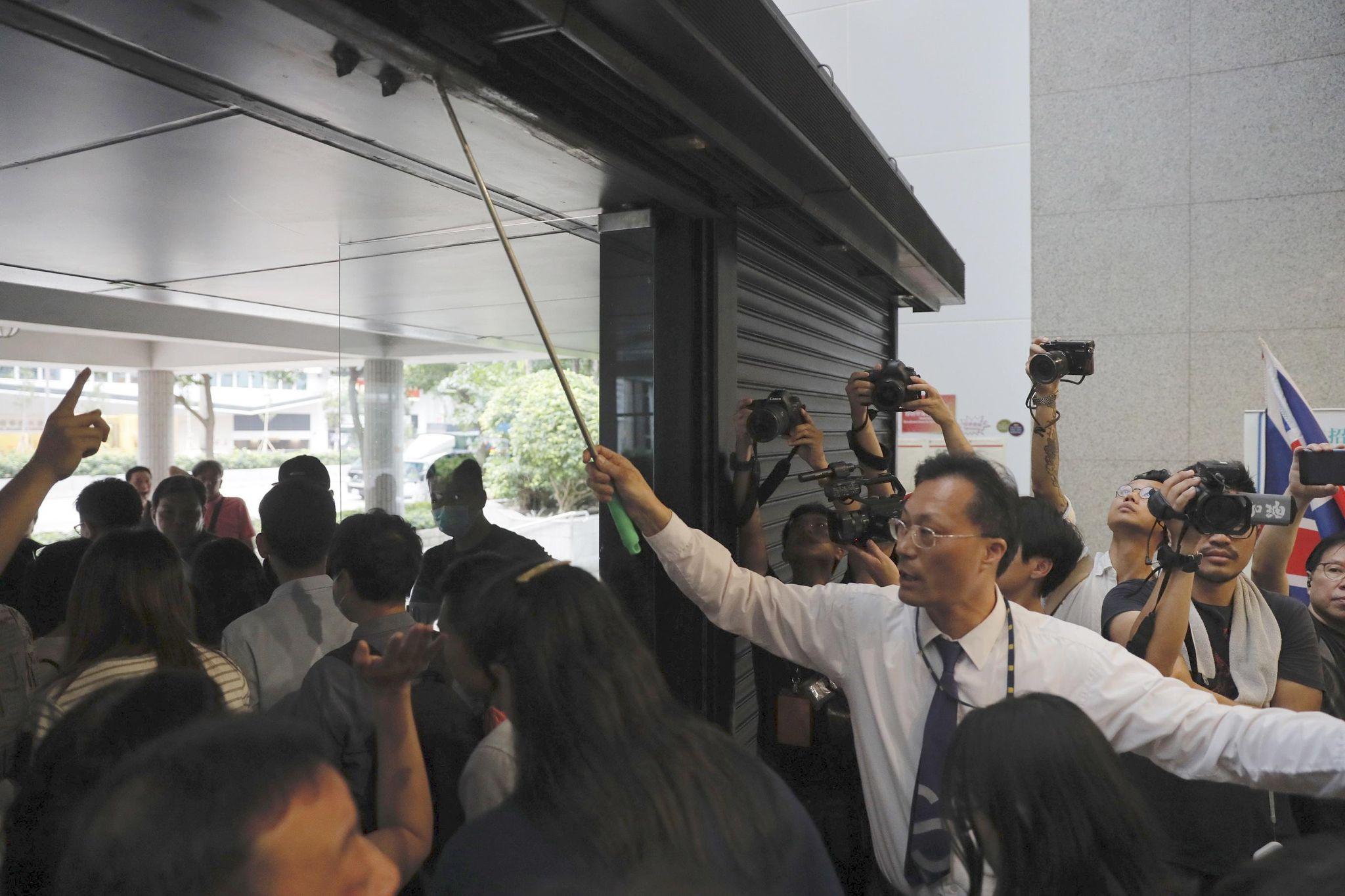 photo image Protesters block Hong Kong building access, plan new action