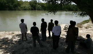 FILE - In this May 25, 2006 file photo, thirty days after crossing into Mexico, Honduran migrants watch from the Mexican side of the Rio Grande as others take a bath as they wait for a good moment to cross the river into the U.S., from the border city of Nuevo Laredo, Mexico. The Mexican border city of Nuevo Laredo is to begin receiving migrants returned from the United States to wait in Mexico while their asylum claims wind their way through U.S. courts, according to Nuevo Laredo Mayor Enrique Rivas on Monday, June 24, 2019. (AP Photo/Dario Lopez-Mills, File)