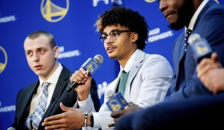 Golden State Warriors NBA basketball draft pick Jordan Poole, center, speaks with reporters on Monday, June 24, 2019, in Oakland, Calif. Fellow incoming Warriors Alen Smailagic, left, and Eric Paschall, right, flank Poole. (AP Photo/Noah Berger)