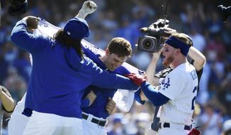 Los Angeles Dodgers' Will Smith, center, has his shirt ripped off by Kenley Jansen, left, and Alex Verdugo after hitting a two-run walkoff home run during the ninth inning of a baseball game against the Colorado Rockies, Sunday, June 23, 2019, in Los Angeles. (AP Photo/Mark J. Terrill)