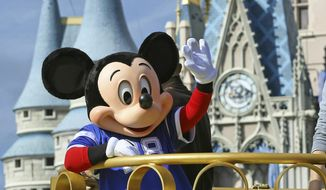 """FILE - In this Feb. 4, 2019, file photo, Mickey Mouse celebrates the Super Bowl winning team, the New England Patriots, during the Super Bowl victory parade in the Magic Kingdom at Walt Disney World in Lake Buena Vista, Fla. Months after workers who play Mickey Mouse and Goofy at Walt Disney World threatened to leave the Teamsters union because of what they called """"horrible misrepresentation,"""" General President James Hoffa has appointed two associates to take over the local union in Orlando, Fla., according to a letter from Hoffa posted Monday, June 24, to the doors of the Local 385 union hall. (Joe Burbank/Orlando Sentinel via AP, File)"""
