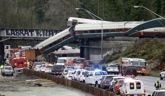 """FILE - In this Dec. 18, 2017, file photo, cars from an Amtrak train lay spilled onto Interstate 5 below as some remain on the tracks above in DuPont, Wash. The National Transportation Safety Board has published its final report Monday, June 24, 2019, on a deadly Amtrak derailment in Washington state in 2017, with the agency's vice chairman blasting what he described as a """"Titanic-like complacency"""" among those charged with ensuring train operations are safe. The train was on its first paid passenger run on a new route from Tacoma to Portland, Oregon, when it plunged onto Interstate 5, killing three people and injuring dozens. (AP Photo/Elaine Thompson, file)"""