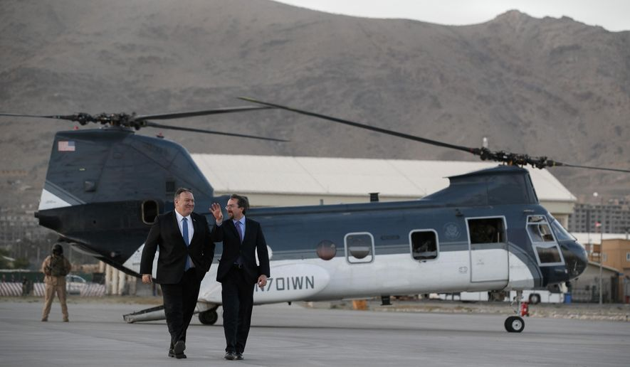 Secretary of State Mike Pompeo, left, walks from a helicopter with U.S. Ambassador to Afghanistan John Bass, Tuesday, June 25, 2019, as Pompeo returns to his plane after an unannounced visit to Kabul, Afghanistan. (AP Photo/Jacquelyn Martin, Pool)