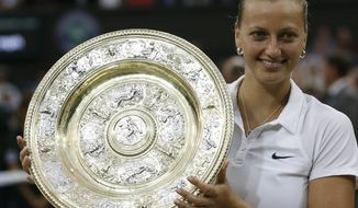 FILE - In this July 5, 2014, file photo, Petra Kvitova, of Czech Republic, holds the trophy after winning the women's singles final against Eugenie Bouchard at the All England Lawn Tennis Championships in Wimbledon, London. Two-time Wimbledon champion Petra Kvitova said on Tuesday June 25, 2019, that she has resumed training and will decide later this week whether she's fit enough to play at the All England Club this year. (AP Photo/Sang Tan, File)