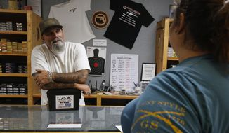 In this photo taken Tuesday, June 11, 2019, Chris Puehse, left owner of Foothill Ammo helps a customer at his shop in Shingle Springs, Calif. Californians will have to undergo criminal background checks every time they buy ammunition starting July 1 under a 2016 voter-approved ballot initiative. (AP Photo/Rich Pedroncelli)