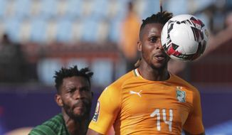 Ivory Coast's Jonathan Kodjia, right, goes for the ball past South Africa's Thulani Hlatshwayo during the African Cup of Nations group D soccer match between Ivory Coast and South Africa in Al Salam Stadium in Cairo, Egypt, Monday, June 24, 2019. (AP Photo/Hassan Ammar)