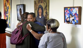 """In this June 11, 2019, photo, Terriz McCleary is embraced by artist Jennifer Coburn, left, while viewing the paintings of """"Souls Shot: Portraits of Victims of Gun Violence"""" exhibited at Einstein Medical Center in Philadelphia. McCleary is the mother of Tamara Johnson, who is seen in the center of the painting at right, """"Beautiful Tamara,"""" by artist Nathalie Miller. McCleary's mother and Tamara's grandmother, Jacqueline Burrell is at right. Coburn is the artist of the portrait of Daronn Davis, pictured in the hoodie behind them. (Tom Gralish/The Philadelphia Inquirer via AP)"""