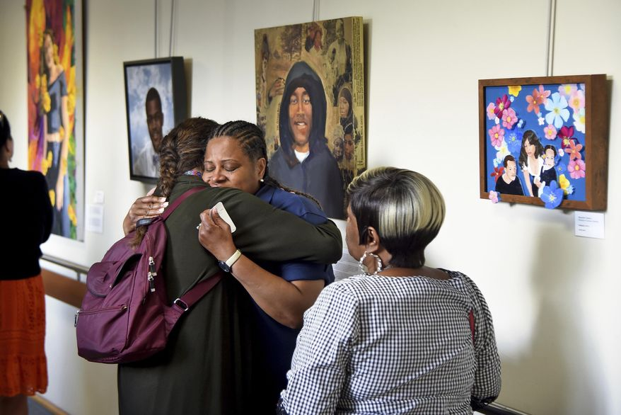 "In this June 11, 2019, photo, Terriz McCleary is embraced by artist Jennifer Coburn, left, while viewing the paintings of ""Souls Shot: Portraits of Victims of Gun Violence"" exhibited at Einstein Medical Center in Philadelphia. McCleary is the mother of Tamara Johnson, who is seen in the center of the painting at right, ""Beautiful Tamara,"" by artist Nathalie Miller. McCleary's mother and Tamara's grandmother, Jacqueline Burrell is at right. Coburn is the artist of the portrait of Daronn Davis, pictured in the hoodie behind them. (Tom Gralish/The Philadelphia Inquirer via AP)"