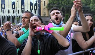 People react while listening to a speaker during a protest as opposition demonstrators gather in front of the Georgian Parliament building in Tbilisi, Georgia, Monday, June 24, 2019. Demonstrators have returned to parliament for daily rallies, demanding the release of detained protesters, the ouster of the nation's interior minister and changes in the electoral law to have legislators chosen fully proportionally rather than the current mix of party-list and single-mandate representatives. (AP Photo/Shakh Aivazov)