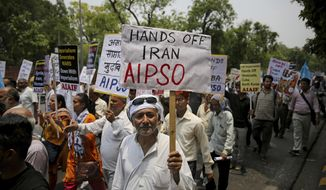 An activist of All India Peace and Solidarity Organization, AIPSO, a left-wing organization, holds a placard during a protest against the upcoming visit of U.S. Secretary of State Mike Pompeo to India, in New Delhi, India, Tuesday, June 25, 2019. Pompeo is scheduled to travel to India after having visited Saudi Arabia and the United Arab Emirates, on a trip aimed at building a global coalition to counter Iran. (AP Photo/Altaf Qadri)