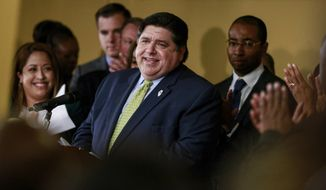 Gov. J. B. Pritzker takes in the applause before signing a bill Tuesday, June 25, 2019 that legalizes adult-use cannabis in the state of Illinois at Sankofa Cultural Arts and Business Center in Chicago. Illinois becomes the 11th to legalize the adult-use of recreational marijuana. (AP Photo/Amr Alfiky)