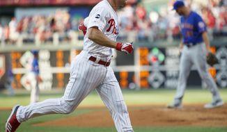 Philadelphia Phillies' Scott Kingery, left, rounds the bases after hitting a home run off New York Mets starting pitcher Walker Lockett, right, during the first inning of a baseball game Tuesday, June 25, 2019, in Philadelphia. (AP Photo/Matt Slocum)