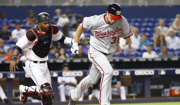 Washington Nationals' Max Scherzer (31) heads to first with a bunt single as Miami Marlins catcher Wilkin Castillo runs after the ball during the fourth inning of a baseball game Tuesday, June 25, 2019, in Miami. (AP Photo/Wilfredo Lee)