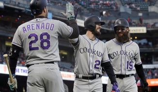 Colorado Rockies' David Dahl, center, is congratulated by Nolan Arenado, left, after hitting a two-run home run that also scored Charlie Blackmon, right, during the third inning of a baseball game against the San Francisco Giants in San Francisco, Monday, June 24, 2019. (AP Photo/Jeff Chiu)